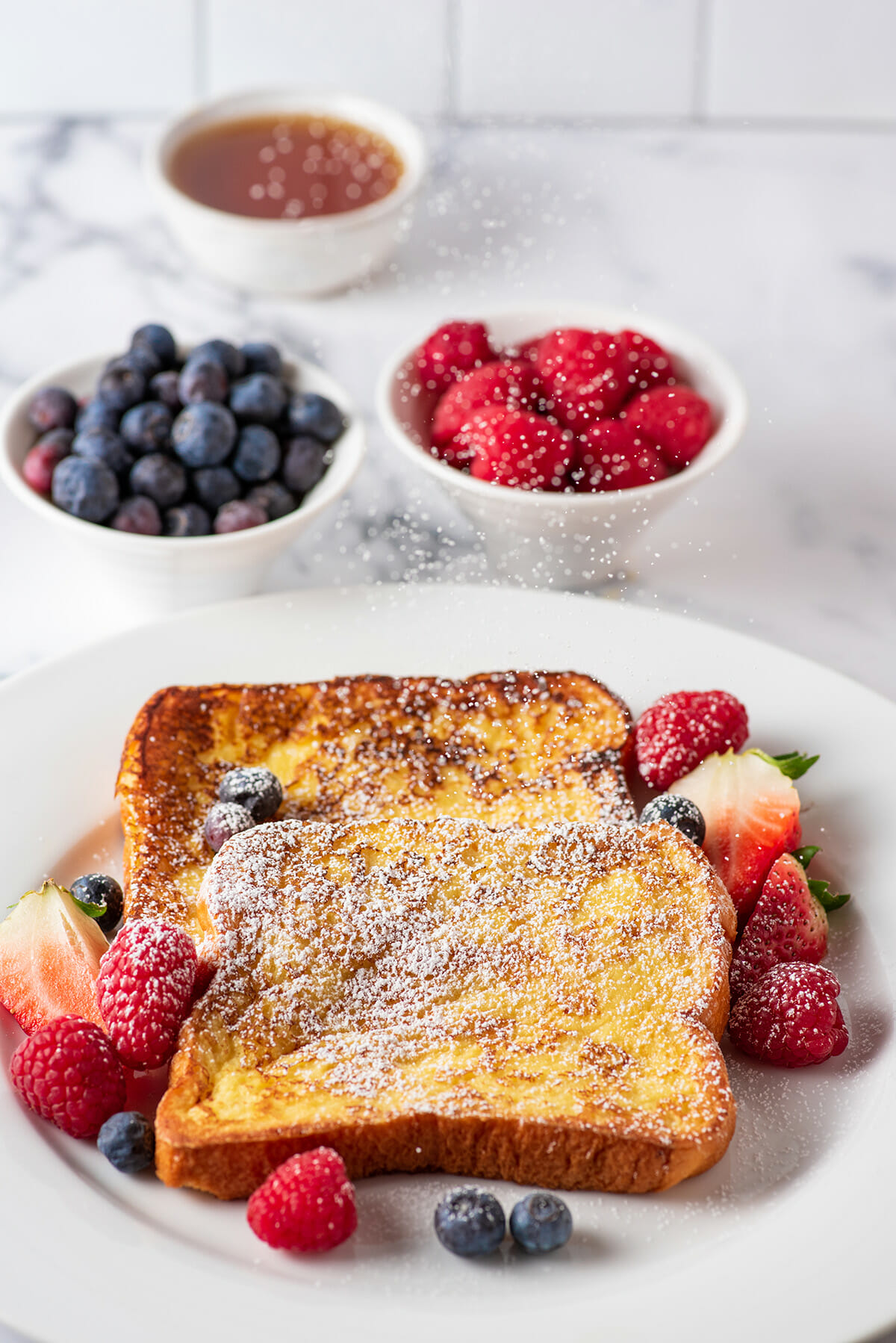 Homemade French toast with berries and powdered sugar.