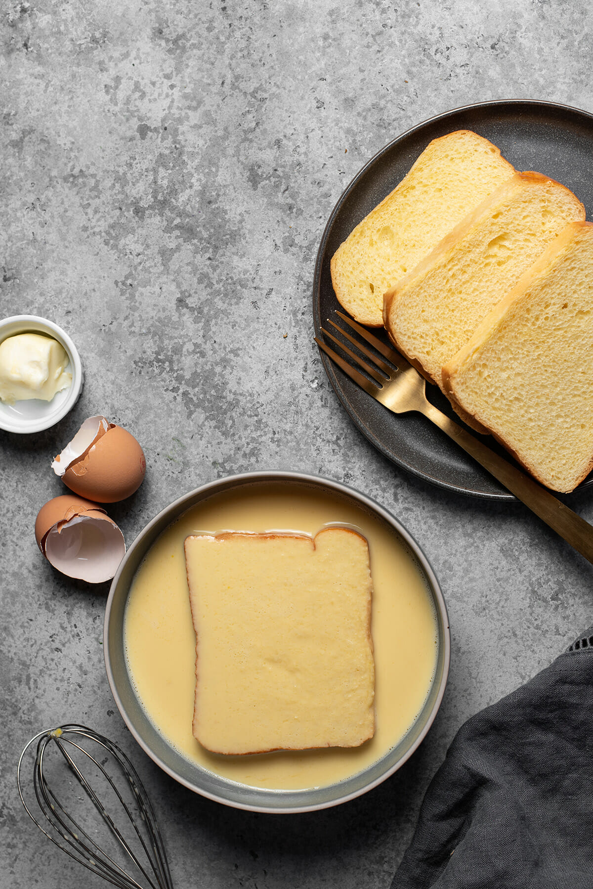 Dunking the bread into egg mixture to make French toast.