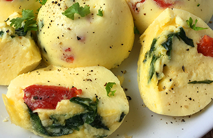 Egg bites from an instant pot loaded with roasted red peppers and fresh spinach.
