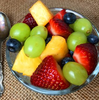 A bowl of fruit salad containing strawberries, grapes, pineapple and blueberries.