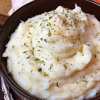 A bowl of mashed potatoes seasoned with garlic and ranch and made in an Instant Pot electric pressure cooker.
