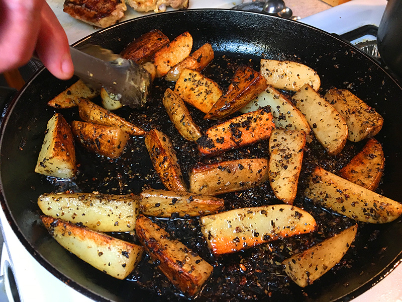 Potato wedges crisping in a pan before cooking with chicken thighs in an Instant Pot