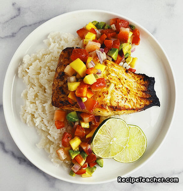 Air fryer citrus garlic salmon served with white rice and mango salad.