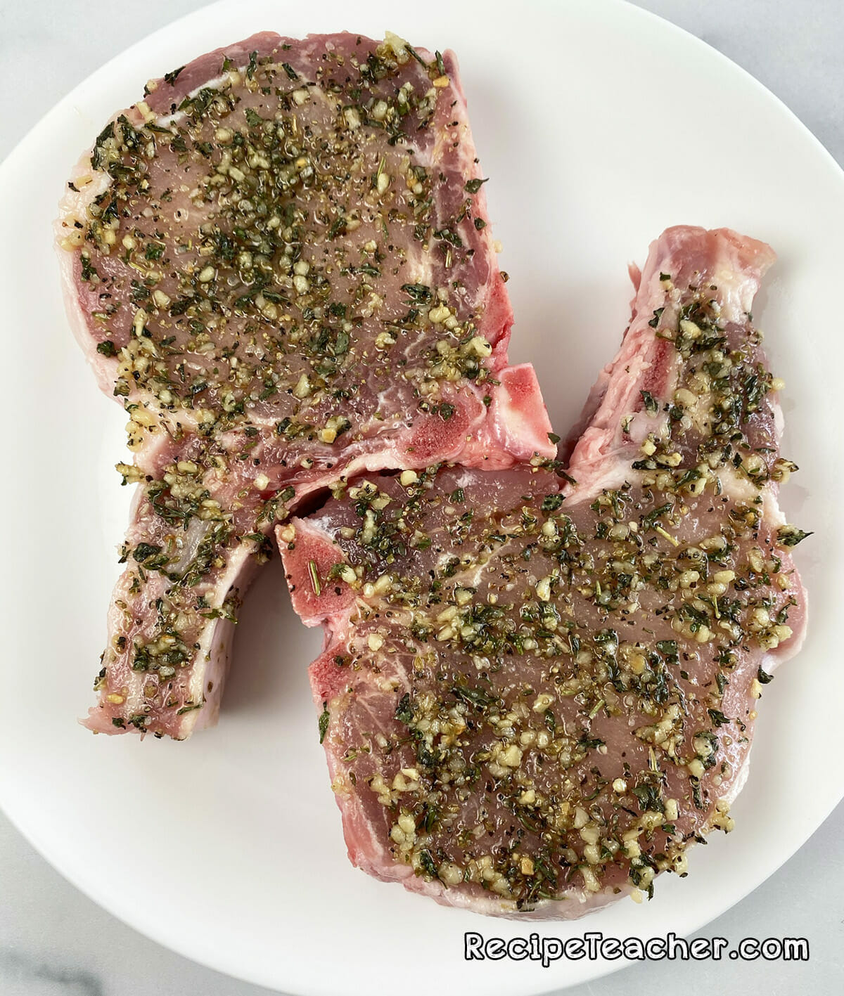 Recipe for thick and juicy air fryer pork chops. Pork chops are seasoned and ready for the air fryer.