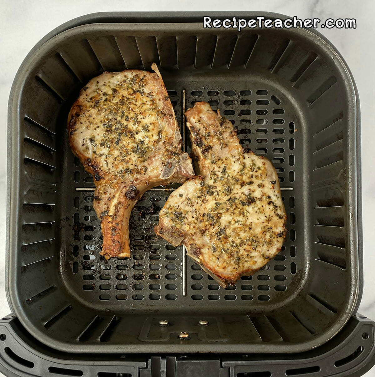 Seasoned thick and juicy pork chops coming out of the air fryer.