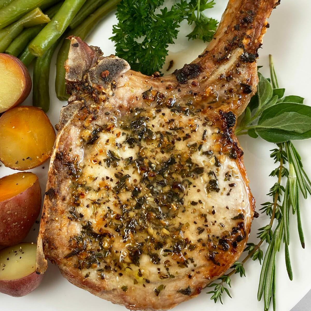 Recipe for thick and juicy, garlic and herb air fryer pork chops.