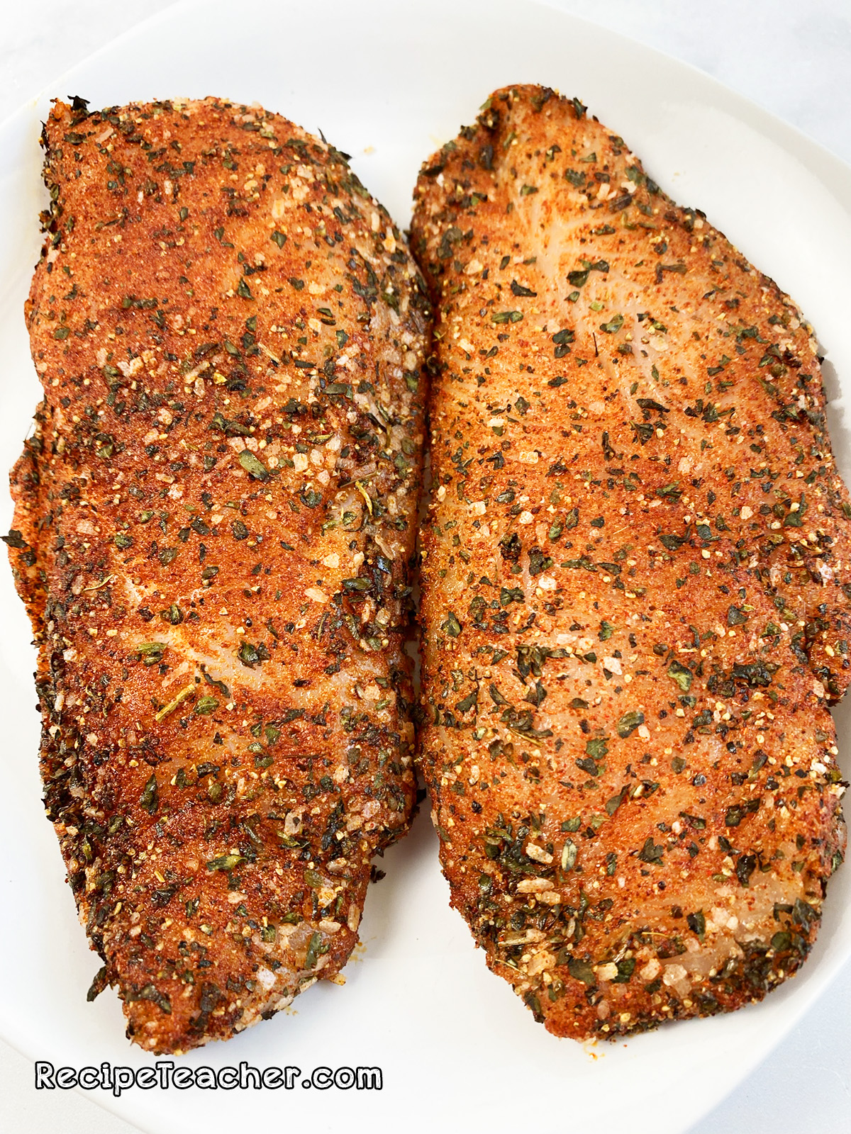 Seasoned chicken breasts ready to be cooked in a George Foreman Grill.